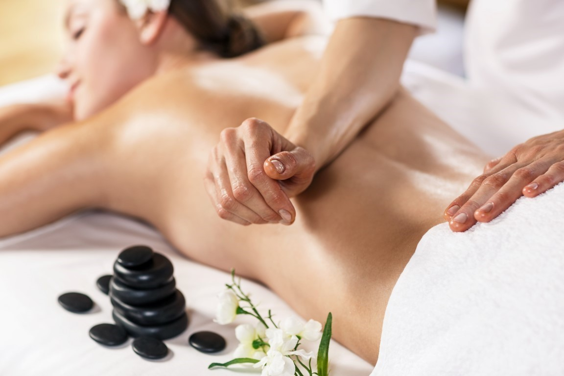 Young beautiful woman enjoying massage on the table at spa center